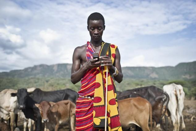 Isaac Mkalia, 20 years old, a teacher by profession is checking his mobil phone.